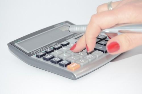 赤いマニキュアの指と電卓