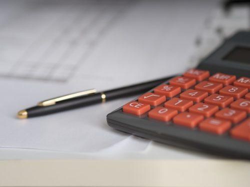 オレンジ色のボタンの電卓とペン