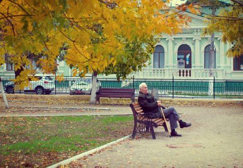 ベンチに座る杖を持った老人
