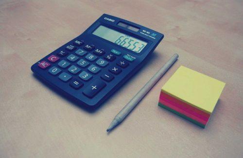 青い電卓とペンと大きめの付箋