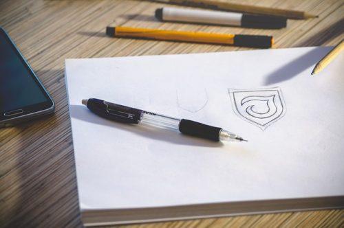 デスクと画用紙と散乱したペン