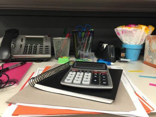 電卓やノートが置かれたデスク