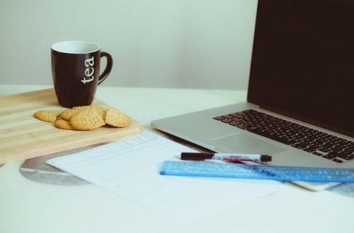 MacBookとマグカップのあるデスク