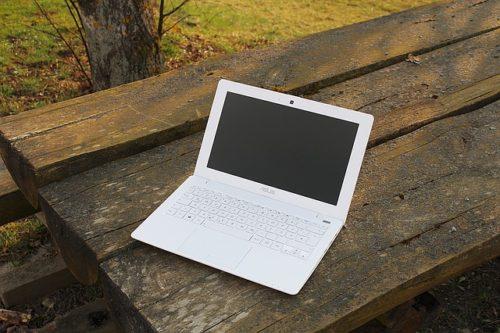木のテーブルに置かれた白いラップトップ